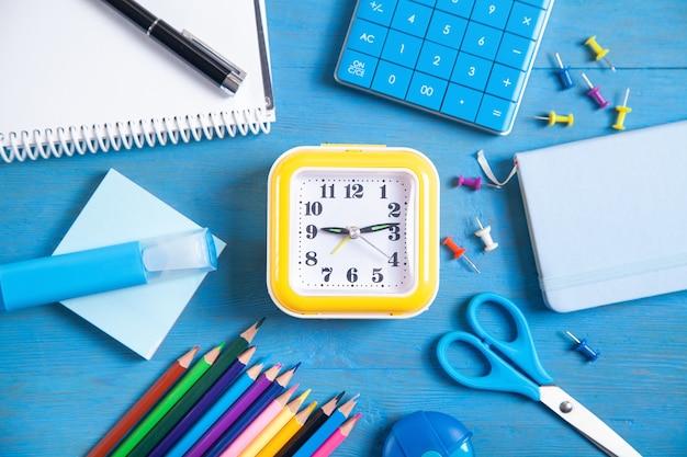 Calculatrice, horloge, crayons, note, marqueur et notes autocollantes sur fond bleu