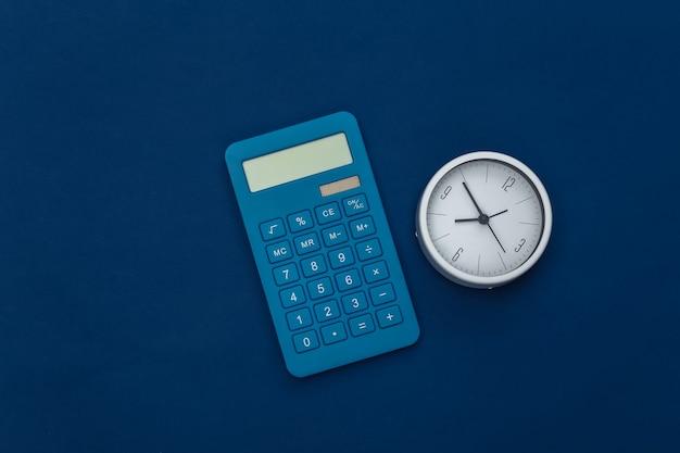 Calculatrice et horloge sur fond bleu classique. couleur 2020. vue de dessus.