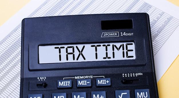 Une calculatrice intitulée temps fiscal se trouve sur la table près du rapport. concept financier