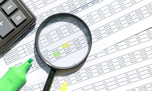 Calculatrice, loupe, marqueurs sur la surface des documents. concept commercial et financier