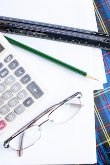 Calculatrice, lunettes, crayon et échelle de rapporteur.