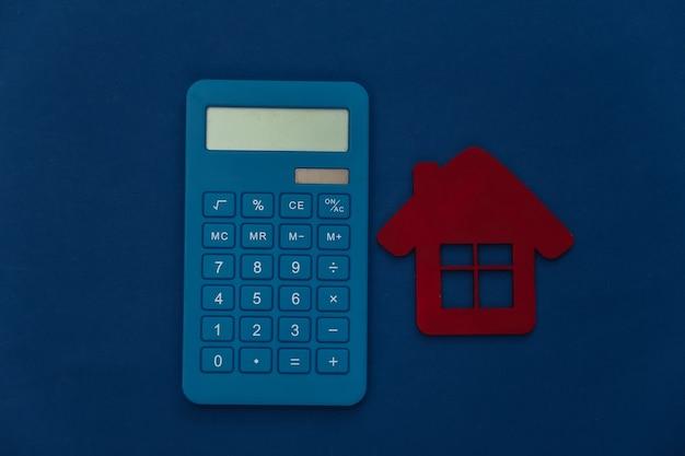 Calculatrice et maison sur fond bleu classique. couleur 2020. vue de dessus