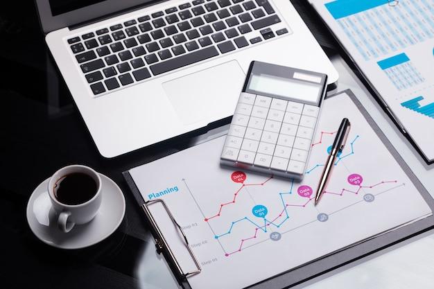 Calculatrice moderne est sur le cahier et sur la feuille avec le calendrier à côté de la tasse de café