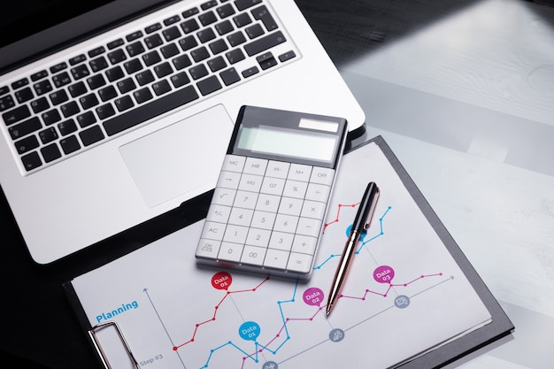 Calculatrice moderne est sur ordinateur portable et sur la feuille avec un graphique