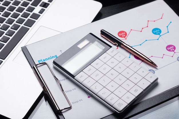 Calculatrice moderne est sur un ordinateur portable et sur une feuille avec un graphique