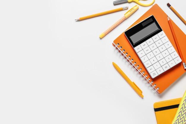 Calculatrice moderne et papeterie sur surface blanche