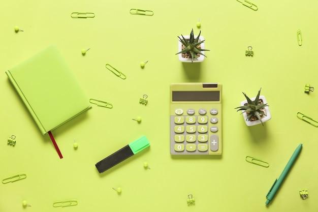 Calculatrice moderne et papeterie sur la surface de couleur