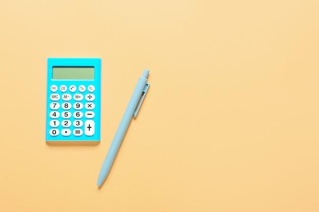 Calculatrice moderne et stylo sur la surface de couleur