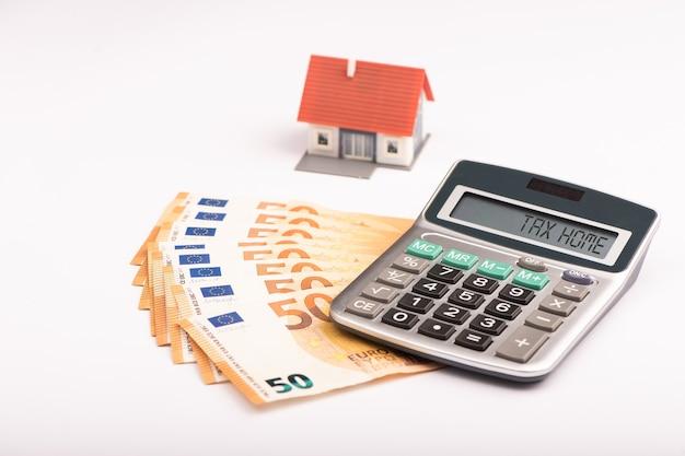Calculatrice, monnaie en euros et maison modèle. concept d'accueil fiscal