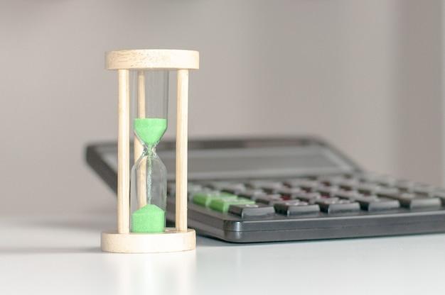 Calculatrice noire et sablier avec close-up de sable vert sur une table en bois blanc, environnement commercial du lieu de travail