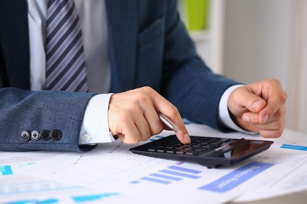 Calculatrice noire et statistiques financières sur l'infographie au gros plan de table de bureau.