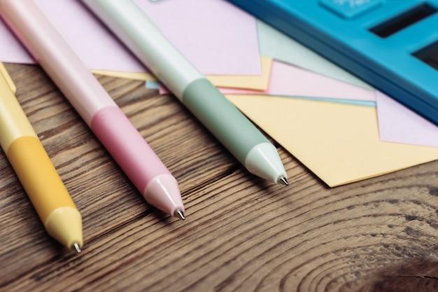 Calculatrice avec papiers mémo et stylos de couleur sur une table en bois.