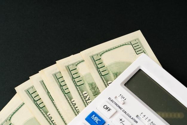 Calculatrice avec pile de dollars américains se bouchent