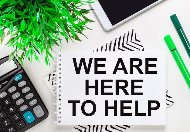 Calculatrice, plante verte, téléphone, marqueur, cahier avec le texte nous sommes ici pour aider sur le bureau. mise à plat.