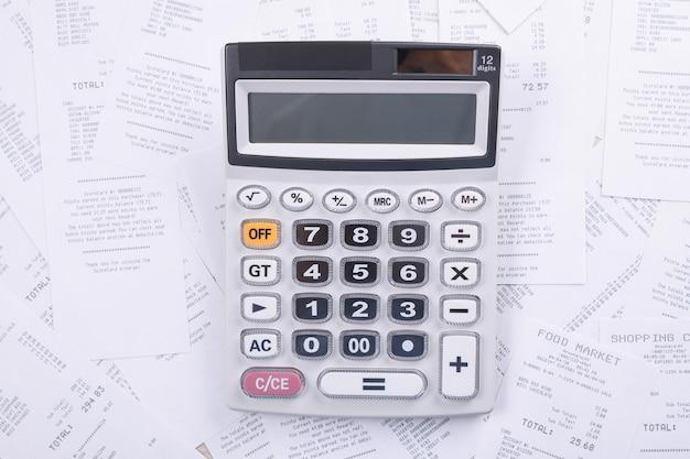 Calculatrice pour compter sur une pile de chèques d'achats au magasin sur un fond en bois. vue de dessus. place pour le texte copiez l'espace