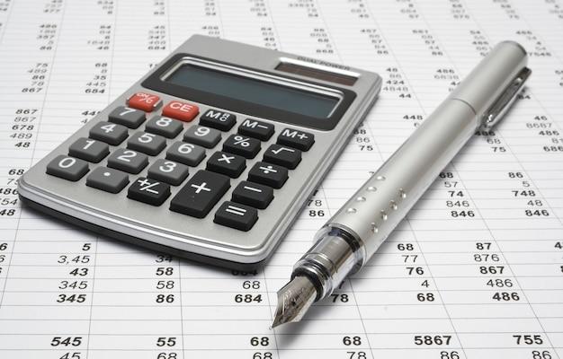 Calculatrice et stylo sur fond blanc
