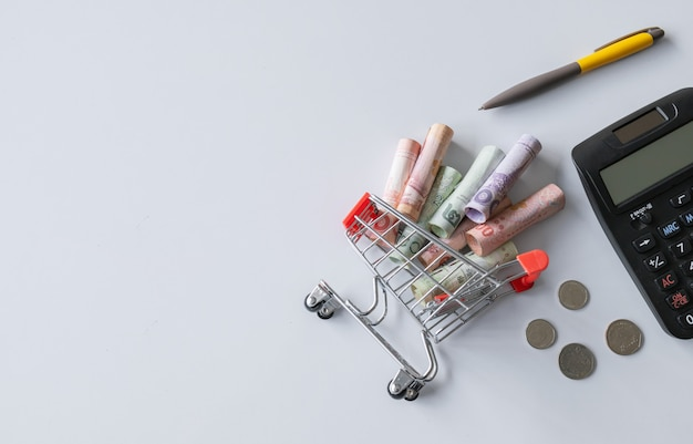 Calculatrice, stylo et panier d'achat avec l'argent (argent thaïlandais) à l'intérieur est à l'envers sur blanc. vue de dessus