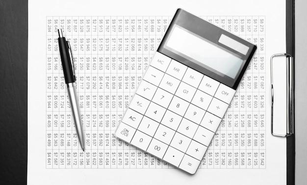 Une calculatrice et un stylo sur les papiers financiers