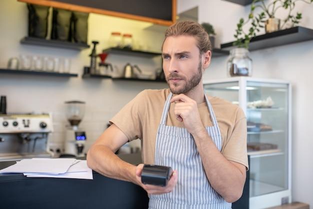 Calculs. jeune adulte pensive homme comptant mentalement debout avec pinpad près de comptoir au café