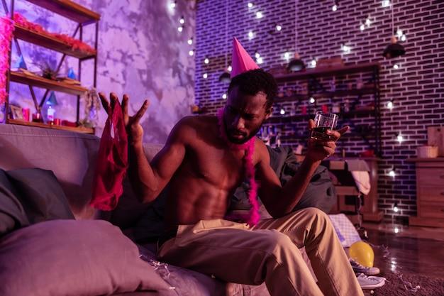 Caleçon rouge à gauche. homme curieux et confus tenant des sous-vêtements féminins d'une main et buvant de l'alcool avec une autre