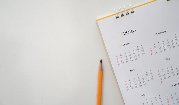 Calendrier 2020 avec un crayon jaune et calendrier mensuel pour prendre rendez-vous