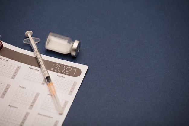 Calendrier 2021 avec seringue et bidon de vaccin, surface bleue