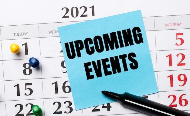 Le calendrier a un autocollant bleu avec le texte événements à venir et un marqueur noir. concept organisationnel. vue d'en-haut