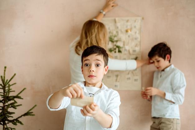 Le calendrier de l'avent accroché au mur. cadeaux surprises pour les enfants. deux garçons émotifs