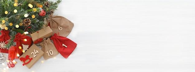 Calendrier de l'avent cadeaux de noël et surprises à côté de branches d'arbre de noël et de lumières brillantes