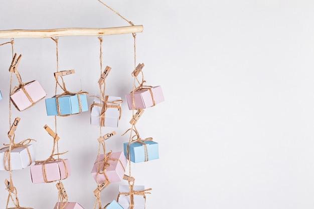 Calendrier de l'avent fait à la main avec des coffrets cadeaux suspendus à des cordes