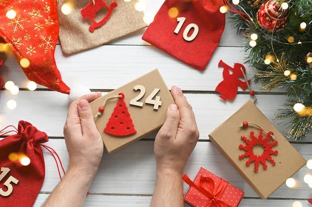 Calendrier de l'avent joyeux noël les mains d'un homme tiennent une boîte cadeau en papier kraft