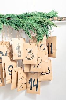 Calendrier de l'avent à la main. sacs-cadeaux accrochés à la corde. concept de bricolage de cadeaux de noël écologiques