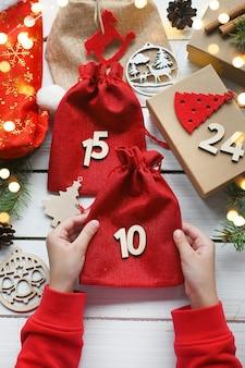 Calendrier de l'avent merry christmas child contient un sac cadeau rouge à côté d'autres surprises et coffrets cadeaux