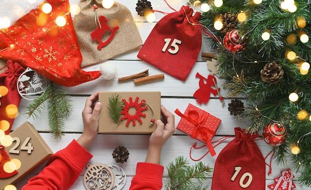 Calendrier de l'avent merry christmashild détient une boîte-cadeau en papier kraft à côté d'autres surprises dans des sacs