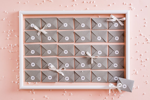 Calendrier de l'avent prêt à l'emploi à partir d'enveloppes en carton gris dans un cadre blanc sur une table dans les décorations de noël