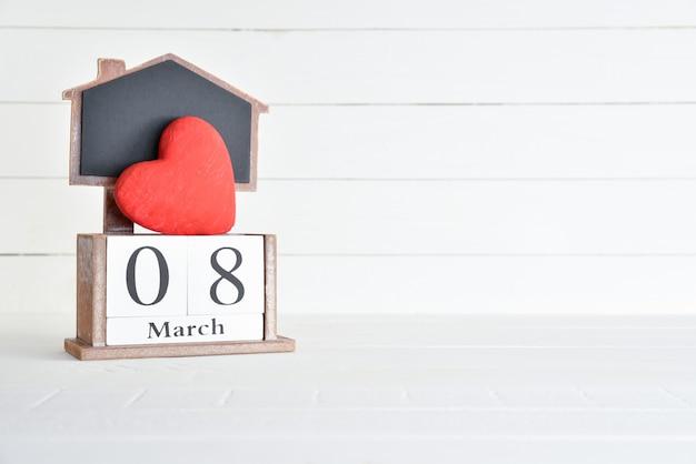 Calendrier de bloc en bois de texte 8 mars avec coeur rouge sur un fond en bois blanc.