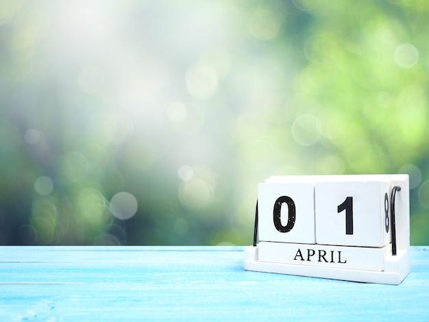 Calendrier de bloc de bois vintage blanc date actuelle 01 et mois d'avril sur une table en bois bleue sur fond abstrait bokeh vert avec espace de copie.