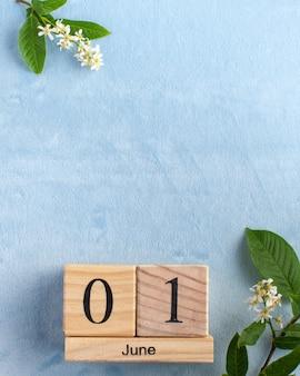 Calendrier en bois 1 juin sur une surface bleue avec des fleurs blanches