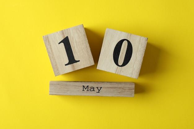 Calendrier en bois avec 10 mai sur fond jaune
