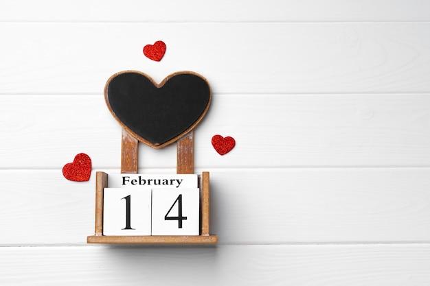 Calendrier en bois 14 février avec des coeurs rouges sur fond de bois blanc vue de dessus