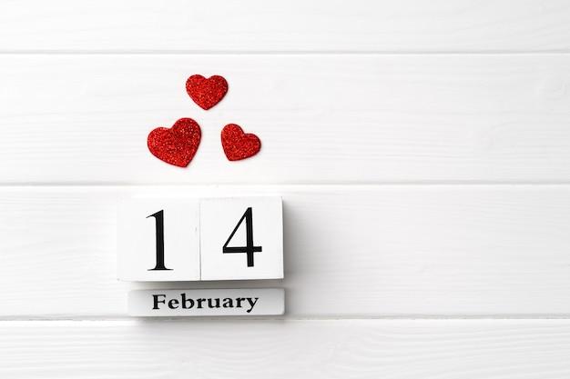 Calendrier en bois 14 février avec des coeurs rouges sur fond de bois blanc