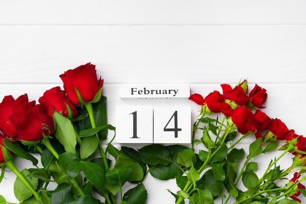 Calendrier en bois 14 février et roses sur fond blanc télévision lay
