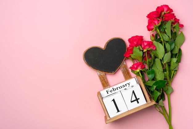Calendrier en bois 14 février et roses sur fond rose à plat