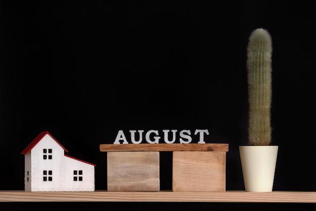 Calendrier en bois d'août, cactus et modèle de maison sur fond noir.