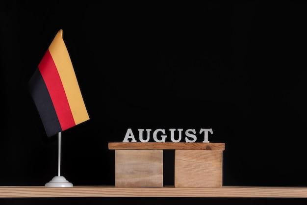 Calendrier en bois d'août avec drapeau allemand sur fond noir