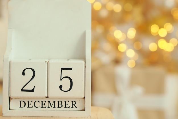 Calendrier en bois blanc avec des cubes et la date du 25 décembre et des lumières bokeh d'une guirlande