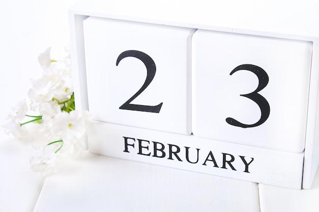 Calendrier en bois blanc avec mot noir du 23 février avec horloge et plante sur une table en bois blanc.
