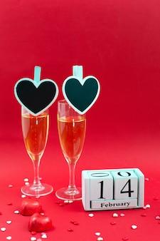 Calendrier en bois avec date du 14 février, bonbons et deux verres à champagne sur fond rouge.