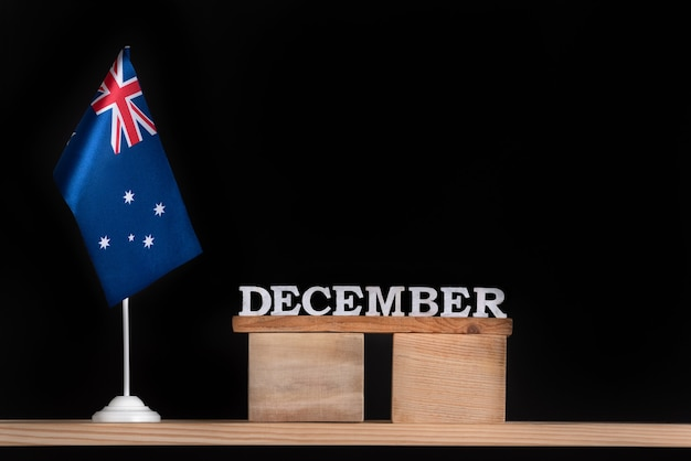 Calendrier en bois de décembre avec drapeau australien sur fond noir. vacances de l'australie en décembre.