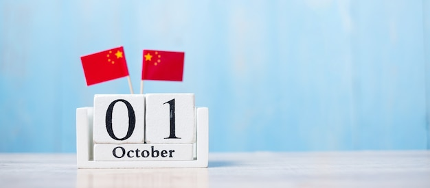 Calendrier en bois du 1er octobre avec des drapeaux miniatures de chine.